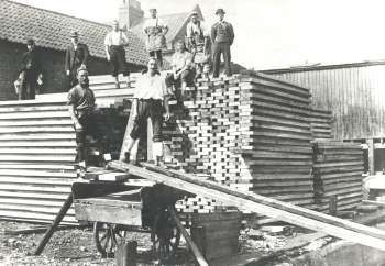 Deal Porters, Surrey Commercial Docks, Rotherhithe, 1910. Moving lengths of timber from ship, warehouse, lorry and barge.  X.jpg