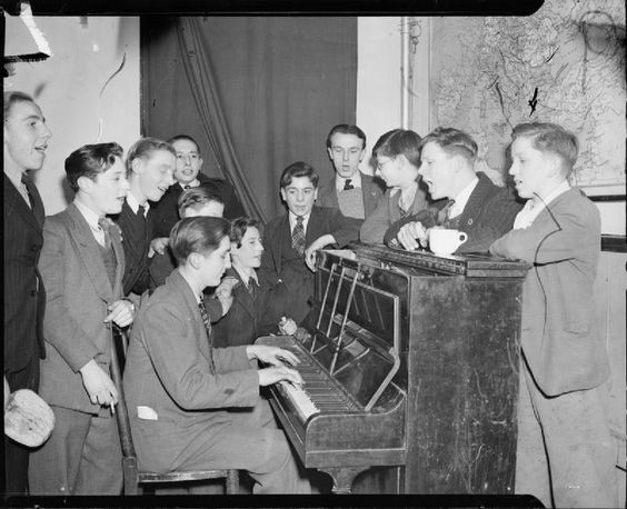 Bermondsey 1944 Boys at the Canterbury Club of the Oxford and Bermondsey Boys Club take part in a sing-song round the piano. The Canterbury Club is on Webb Street, Bermondsey.jpg