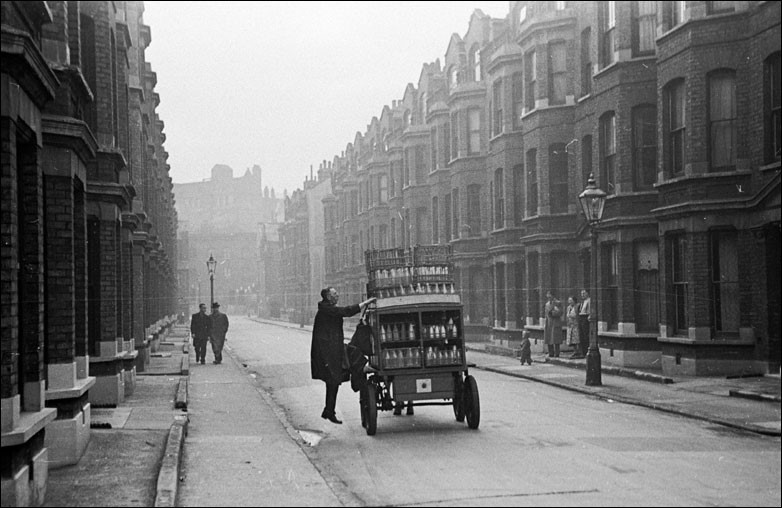 A man climbs onto a Southwark milk cart near the Elephant and Castle in South London..jpg