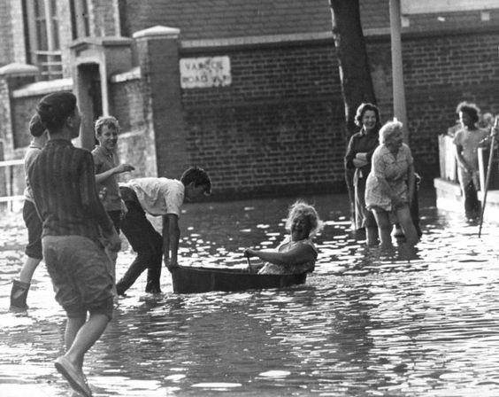 A resident paddle down her flooded street in a bath tub when a water main burst in South Bermondsey.jpg