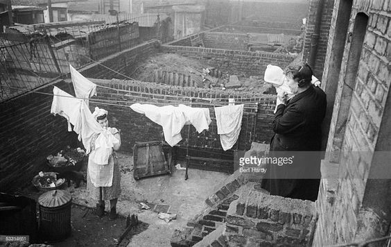 A woman and baby look on as a Southwark housewife hangs out her washing in the Elephant and Castle area of south London, 8th January 1949.   X.jpg