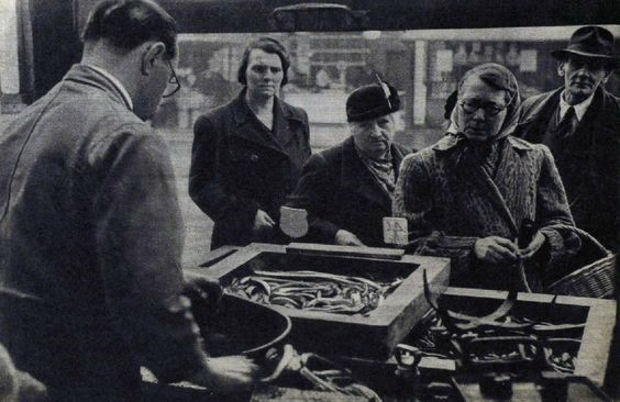 An eel stall at Elephant and Castle. Hot, a shilling a basin, jellied, two shillings. 1949   X.jpg