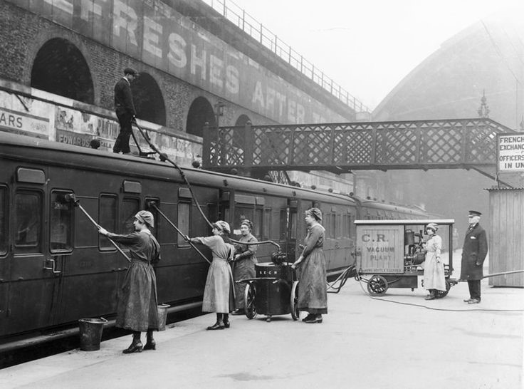 Women workers using an industrial vacuum cleaner to clean railway carriages at London Bridge Station..jpg
