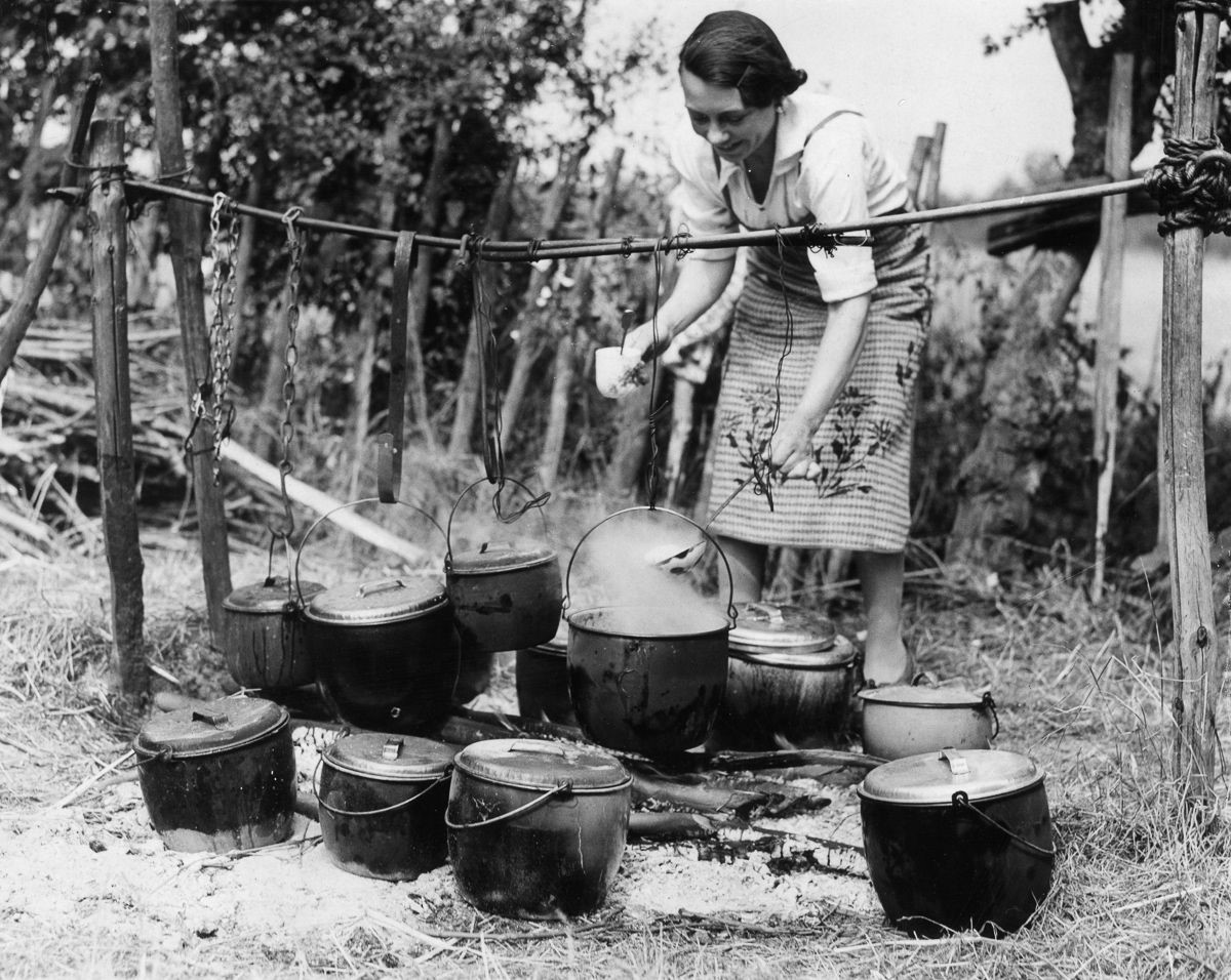 A woman prepares a meal for hop pickers at the Whitbread hop camp in Paddock Wood, Kent. (1937).jpg