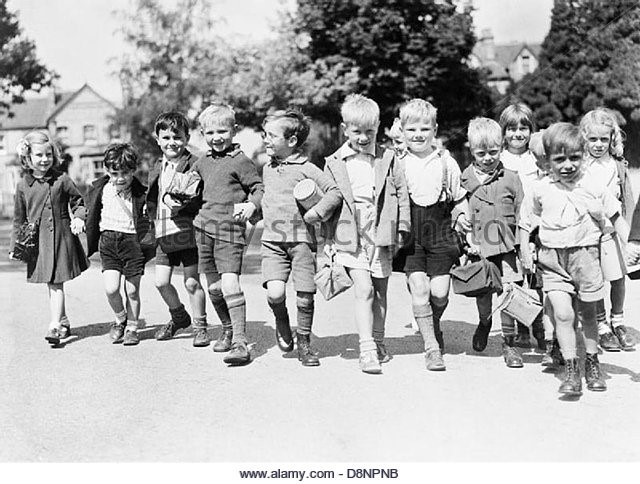 A group of smiling evacuees from Rotherhithe, with gas mask boxes hold hands on a walk in Reading  c1940..jpg