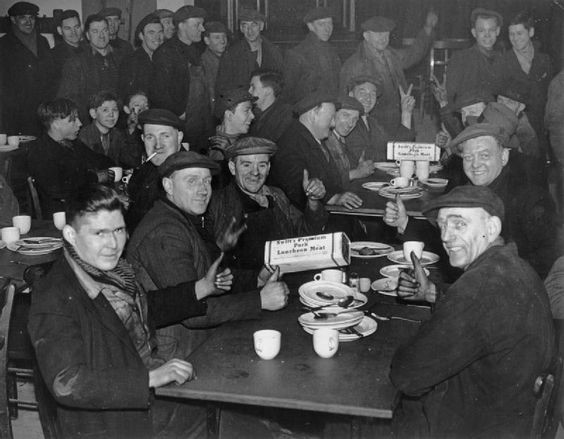 Dock workers give the thumbs up and V signs as they lunch on American canned meat at a London Dockworkers Canteen, London, 1941..jpg