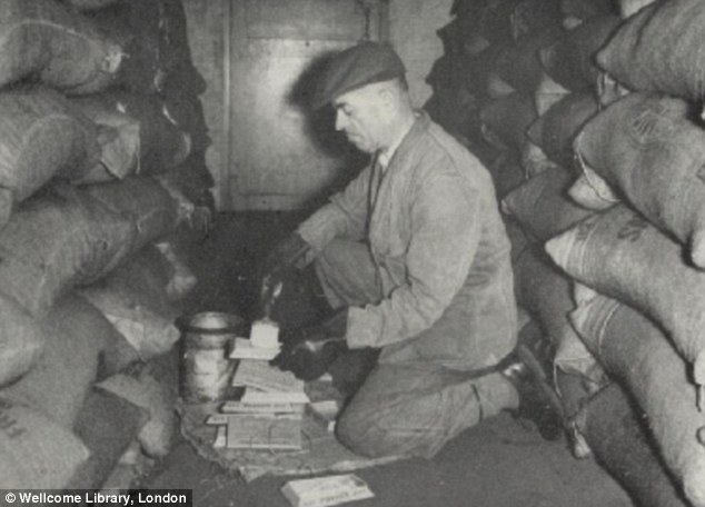 Another worker prepares deadly bait for the rats on what is described as a Bermondsey 'rat run' 1957.  X.png