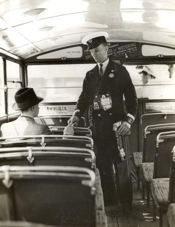 Conductor (badge no N65108) issuing a ticket to a passenger on the lower deck of a bus at London Bridge; the conductor has a Bell Punch ticket machine .  X.jpg
