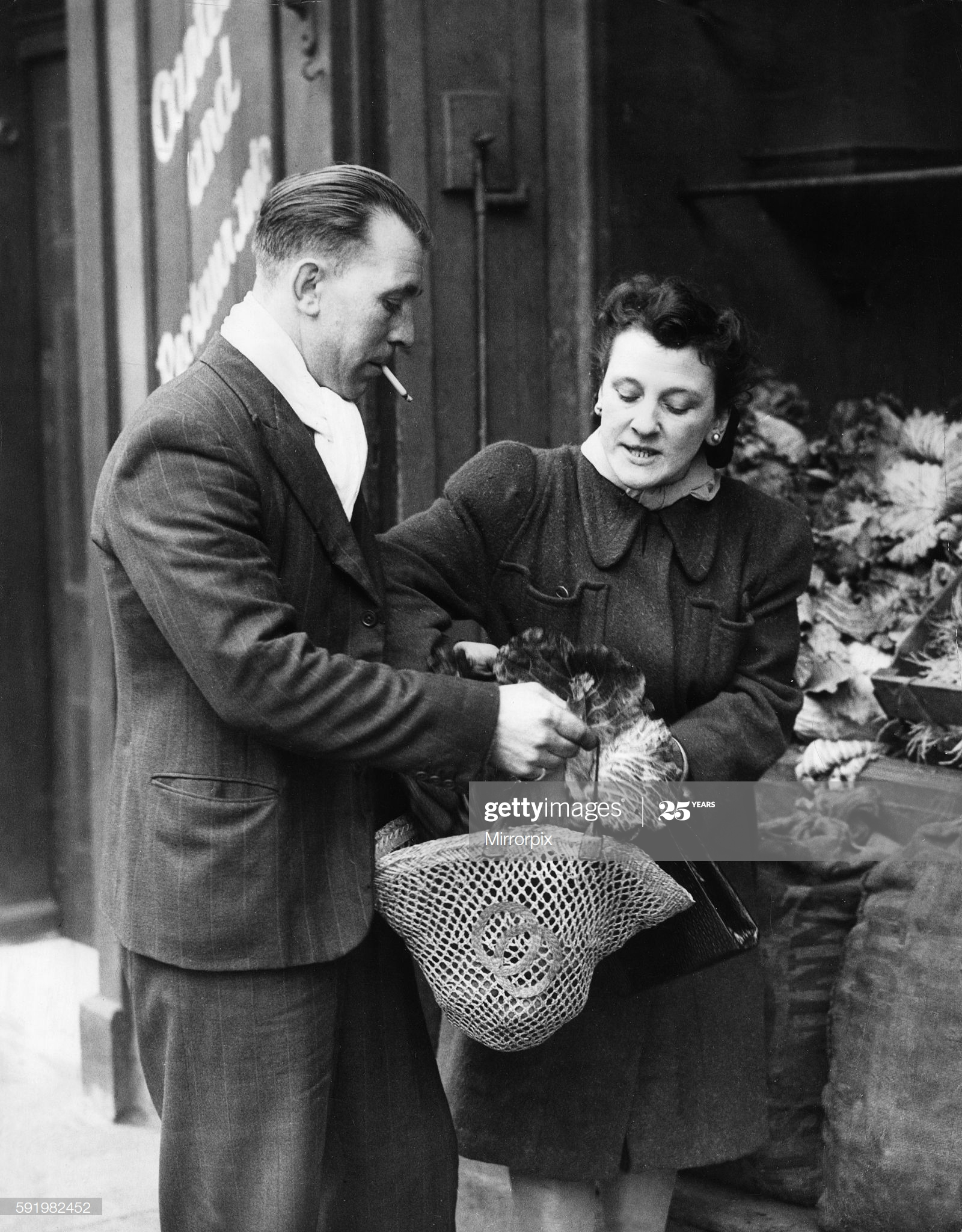 Private Ted Saunders of the 2nd Army out shopping with his wife Margaret in Bermondsey while on leave during the Second World War. 7th January 1945.  X.png