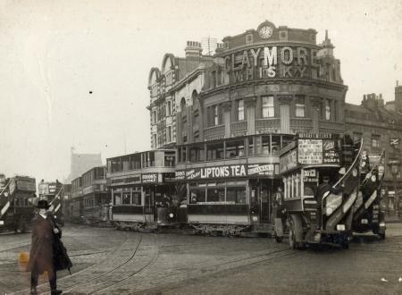 Elephant and Castle, street scene featuring a line of electric trams and motor buses 1920.png