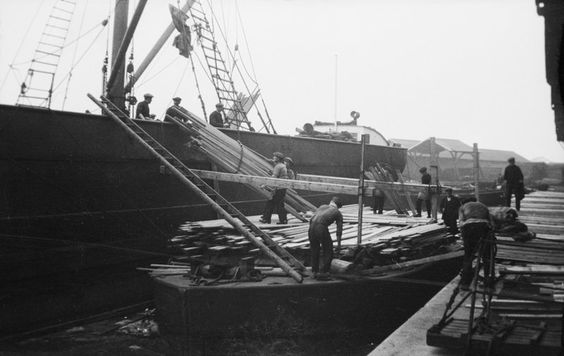 Discharging deals, battens and boards from the SS 'Portos' at Russia Dock, Rotherhithe. Deal was a softwood timber that was imported to the Surrey Docks.   X.png