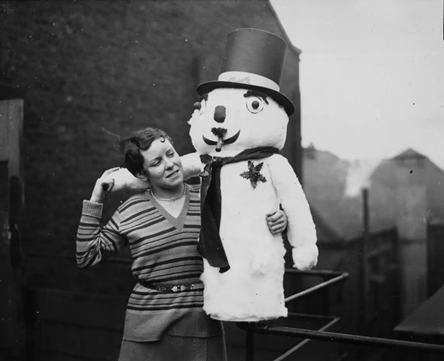 Blackfriars Road 1930.A young girl with a toy-filled snowman at Messrs Pascalls in Blackfriars, London.   X.png