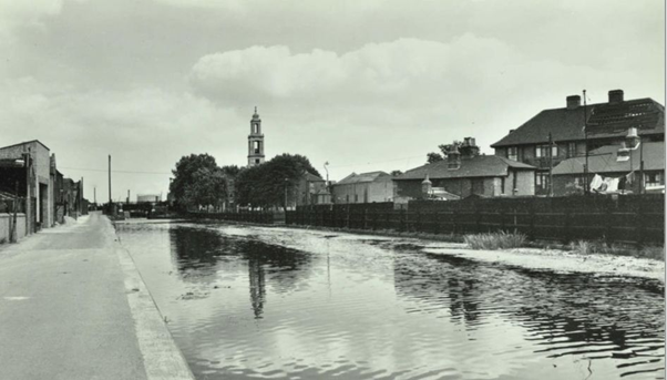 Surrey Canal c1956, when it was still water-filled, west of the Wells Way bridge (in the distance with St Georges Church to its right).  X.png